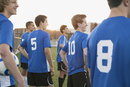 Side view of soccer players watching game on field.