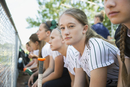 Portrait confident middle school girl with softball team on bench