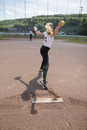 Middle school girl softball pitcher pitching ball on baseball diamond