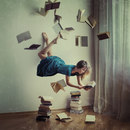 Woman reading book in mid-air with books flying around