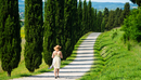 Woman in sunhat and summer dress walking on treelined footpath