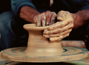 Hands of potter working with clay on wheel