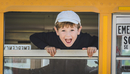 Cheerful boy (8-9) looking out schoolbus window