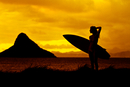 Silhouette of woman with surfboard against sunset sky, Oahu, Hawaii, USA