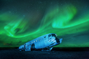 Aurora dancing over the wreck of an airplane.