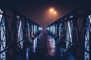 Person walking over foggy bridge at night, Cluj-Napoca, Romania