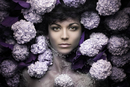 Portrait of young woman in water with hydrangeas
