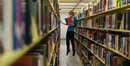 Young man reading book and levitating in library, Fullerton, California, USA