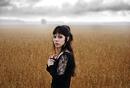 Portrait of woman standing in field of grain