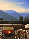 Cheese fondue on balcony with mountains in background, Switzerland