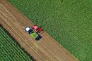 Top view of tractors harvesting crops in field