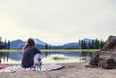 Woman sitting on lakeshore at dusk