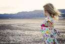 Side view of thoughtful girl standing on arid landscape