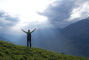 Rear view of female hiker standing with arms outstretched on mountain against cloudy sky