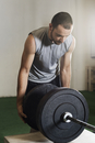 Male athlete fixing barbell in gym