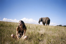 Thoughtful woman sitting on landscape with elephant in background