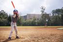 Side view of boy swinging baseball bat on field