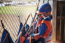 Side view of boy removing baseball bat from bag at field