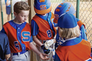 Baseball player giving bubble gums to friends on field