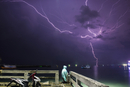 Man sitting at pier by sea against lightning in purple sky