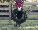 Low section of woman holding wreath while standing against wooden fence in backyard