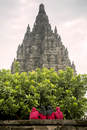 Rear view of women standing at Prambanan temple against clear sky