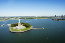 High angle view of Statue of Liberty on island amidst sea against blue sky