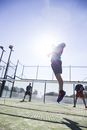 Male athletes practicing tennis in court against sky on sunny day