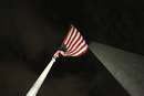 Low angle view of American flag by Washington Monument against sky