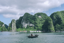 Man sitting in boat at Halong bay by mountains against cloudy sky