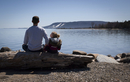 Rear view of father and daughter sitting on log at lakeshore against clear sky during sunny day