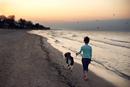 Woman walking her dog on beach