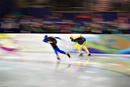 Two speed skaters rounding track curve during race