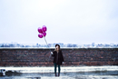 Woman on rooftop holding balloons