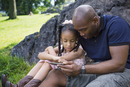 Father and daughter (6-7) sitting on grass and playing with digital tablet in park rock in background