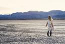 Rear view of girl walking on arid landscape