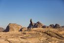 Rear view of woman walking on rocks against clear blue sky