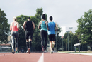 Rear view of athletes running on track