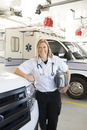 Portrait of female EMT standing by ambulance