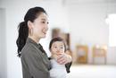 赤ちゃんを抱き抱えて微笑む女性