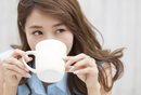 微笑みながら両手でカップを持つ女性
