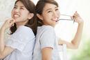 背中を合わせて微笑む2人の女性