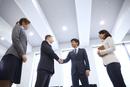 オフィスで握手をするビジネス男性