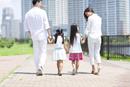 手をつないで遊歩道を歩く家族の後ろ姿