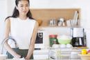 キッチンで食器を洗う女性