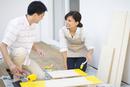 ベニヤ板にペンキを塗る男性と女性
