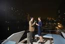 夜景をバックにクルーザーの上で乾杯するカップル