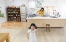 キッチンに立つ母親と遊ぶ子供