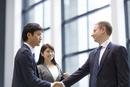 オフィスビルのエントランスで握手をするビジネス男性