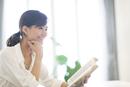 手に本を持ち微笑む女性